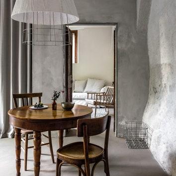 Кухня. Стол и стулья винтажные; светильник изпроволоки сделан авторами проекта идекорирован гипсовымбинтом. Накаменной стене справа теплоизоляционное покрытие, MantiCeramic.