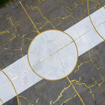 Баскетбольная площадка с золотыми трещинами