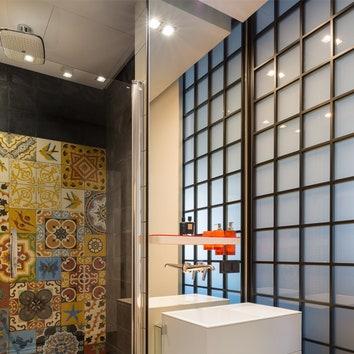 """Если во всех остальных помещениях квартиры цвет использован точечно, то ванные комнаты — это цветовой всплеск. Дизайнеры не смогли ограничиться какой-то одной коллекцией французской плитки Carocim из """"Греты Вульф"""" и собрали микс из разных. Для усиления контраста появился строгий черный общий фон, который добавил ванным комнатам объема."""