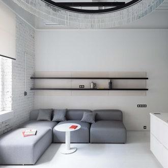 Зона гостиной. Диван и журнальный столик, Delo. Преимущество этой небольшой квартиры в том, что в ней три окна: одно в гостиной и два в спальне.
