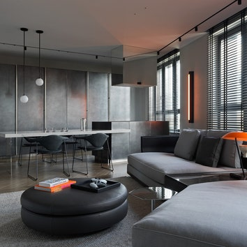 Минималистичная квартира в Москве, 100 м². Вид из гостиной на кухню. Диван, пуф, и приставной столик Minotti, бра Pelle, настольная лампа Astep.